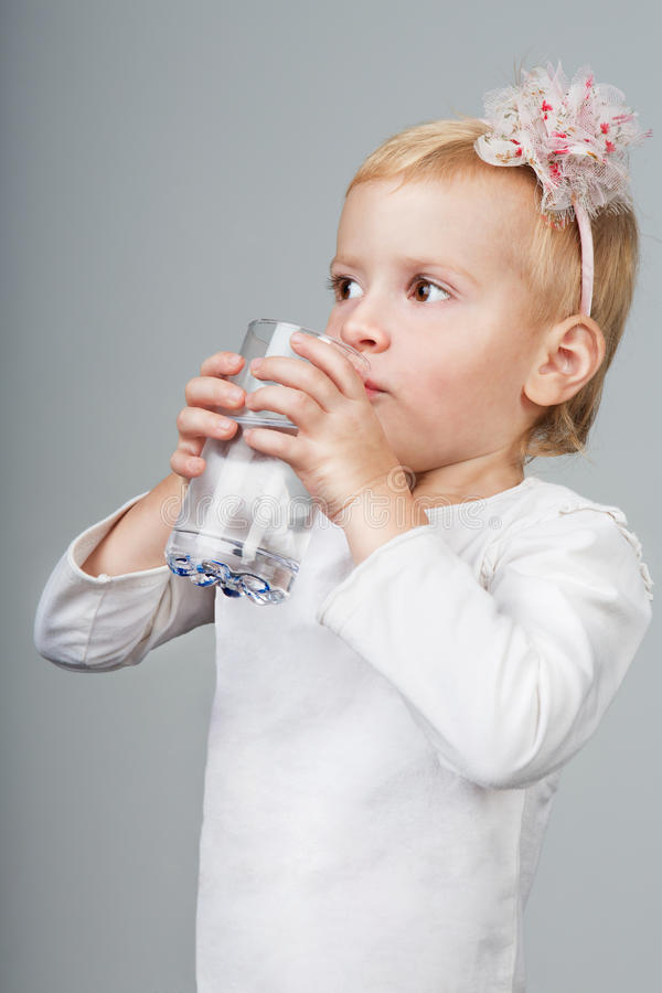 Girl drink water from a glass. Little girl holding glass of water on grey background. Studio shot royalty free stock image