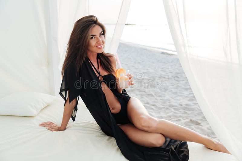 Girl drinking cocktail at the beach royalty free stock image