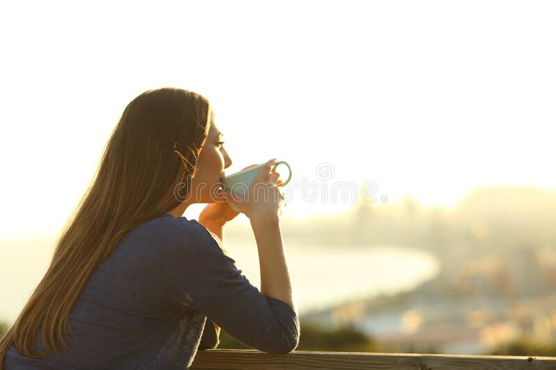 Girl drinking coffee contemplating views at sunset royalty free stock images
