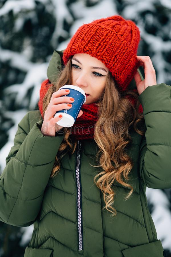 Girl drinking coffee in snowy winter day. Girl drinking coffee in the winter cold day. Young girl in winter knitted red hat and scarf drinking coffee in a snowy royalty free stock images