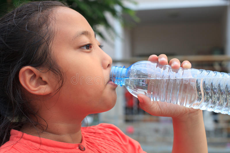 Girl drinking fresh water from plastic bottle stock photos