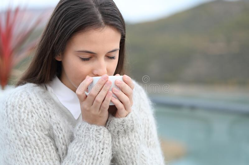 Girl drinking hot coffee in a restaurant terrace stock images