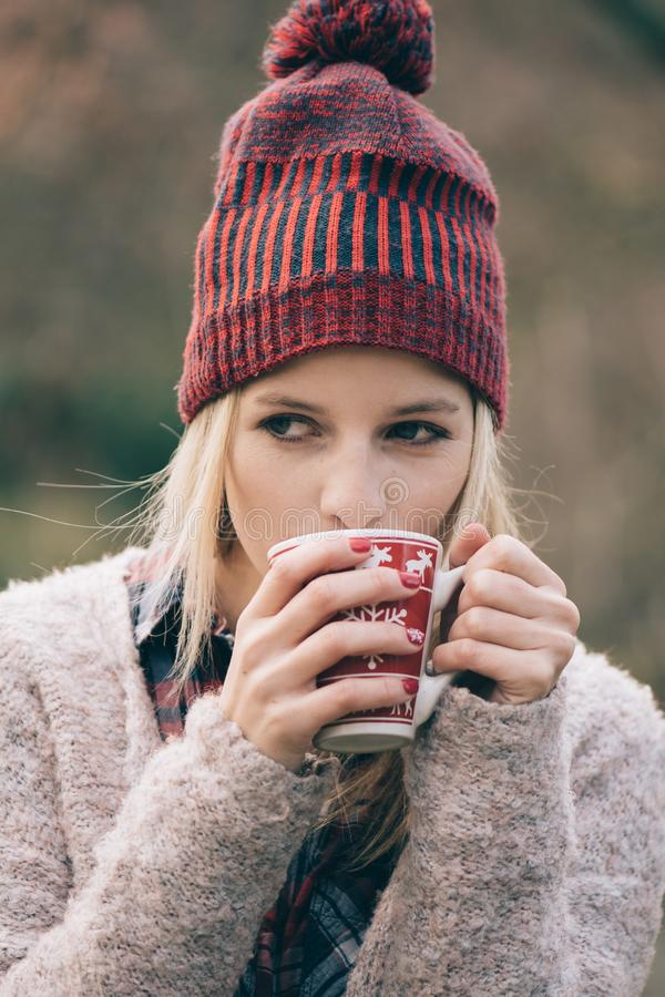 Girl drinking hot drink outdoor. Coffee or drink in mug. stock photo