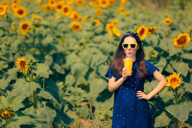 Woman Drinking Juice in Summer Sunflower Field stock image