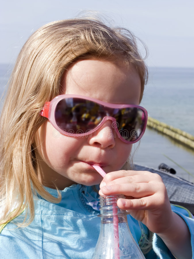 Girl drinking with a straw stock image