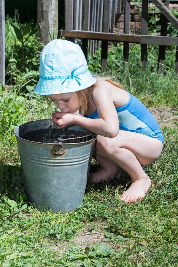 Girl drinking water from a bucket royalty free stock photography
