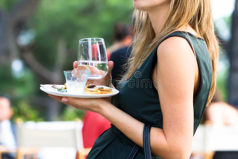 Girl drinking water. A girl drinking a glass of ice water to a festivity stock image