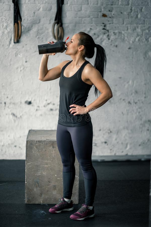 Girl drinking water in gym after workout stock photo