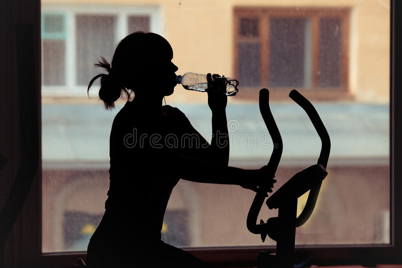 Girl drinking water in a gym. Silhouette stock photos