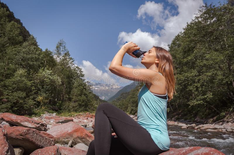 Girl drinking water and sitting on stone in a river royalty free stock image