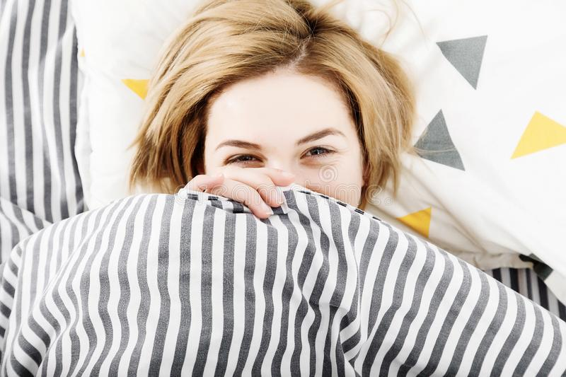 The girl drinks coffee in bed. Morning girl The young girl wakes up in the morning. Sleep. Morning awakening. Reading the press in royalty free stock image