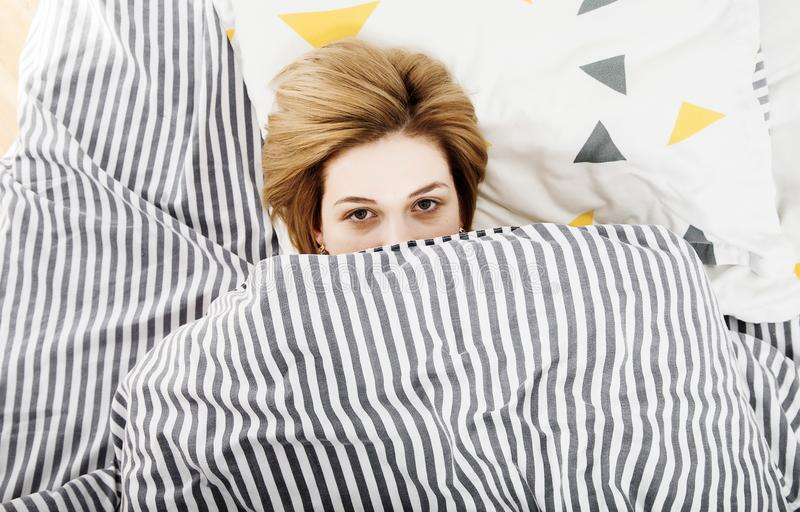The girl drinks coffee in bed. Morning girl The young girl wakes up in the morning. Sleep. Morning awakening. Reading the press in royalty free stock images