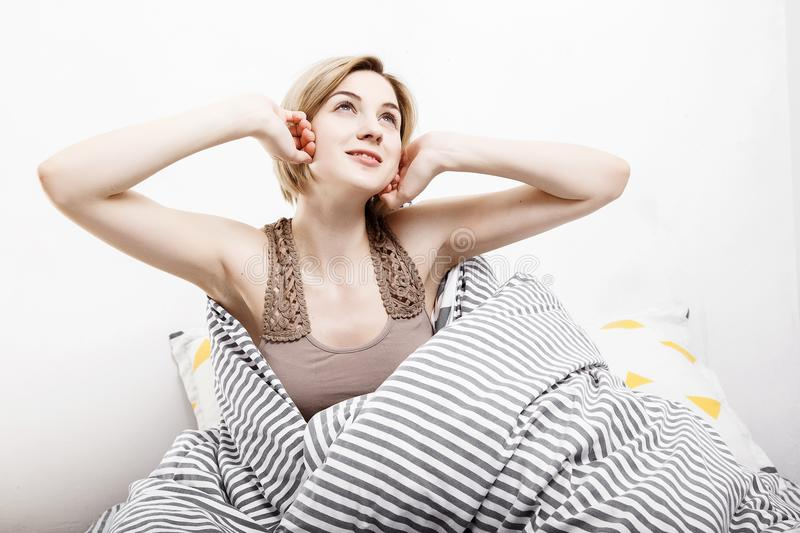 The girl drinks coffee in bed. Morning girl The young girl wakes up in the morning. Sleep. Morning awakening. Reading the press in royalty free stock photos
