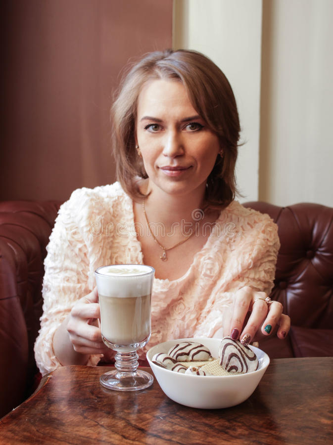 The girl drinks coffee with biscuits royalty free stock photography