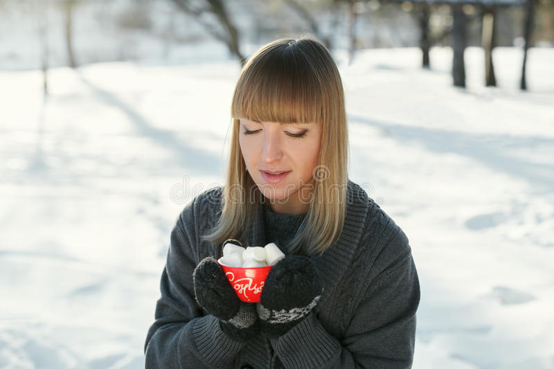 Girl drinks coffee with marshmallows in the winter outdoors. With red circles and looking at the camera. On the mug is written in the sun royalty free stock images