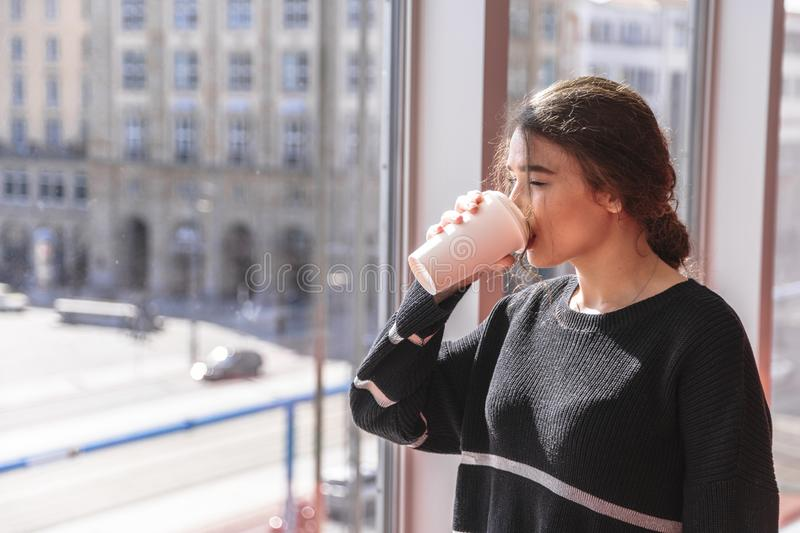 Girl drinks coffee and stands by panoramic window stock photography