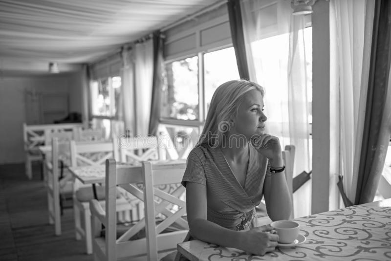 Girl drinks coffee or tea in cafe or restaurant. royalty free stock images