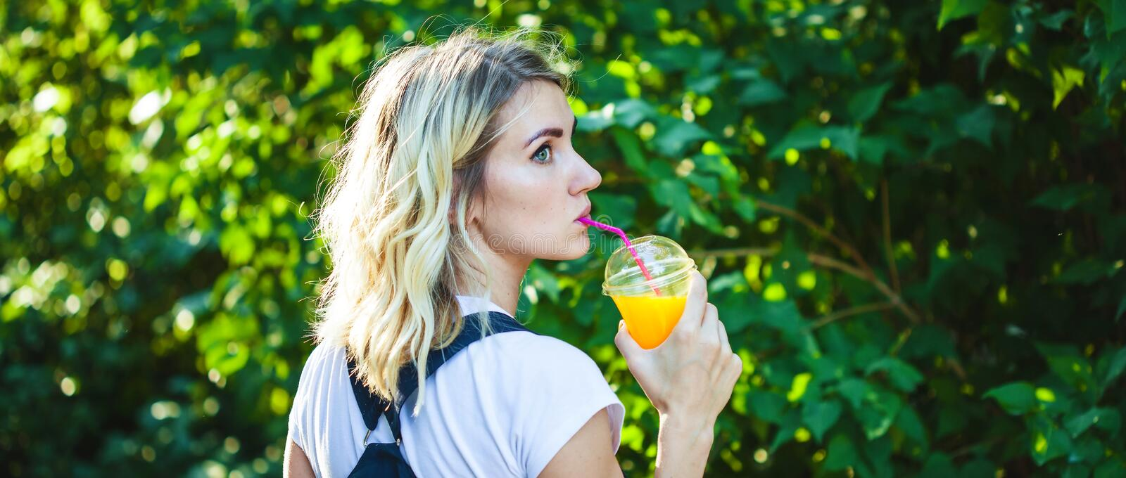 A girl drinks freshly squeezed juice, a healthy lifestyle Banner concept. stock photo