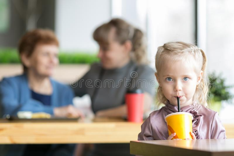 The girl drinks juice on the background of his mother and grandmother. A small child alone drinks a cocktail from the tub and the mother and grandmother are royalty free stock images