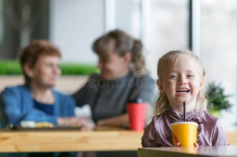 The girl drinks juice on the background of his mother and grandmother. A small child alone drinks a cocktail from tub and the mother and grandmother are talking stock images