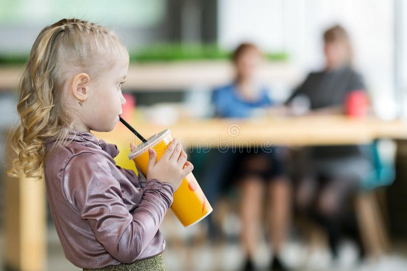 The girl drinks juice on the background of his mother and grandmother. A small child alone drinks a cocktail from tub and the mother and grandmother are talking stock photos