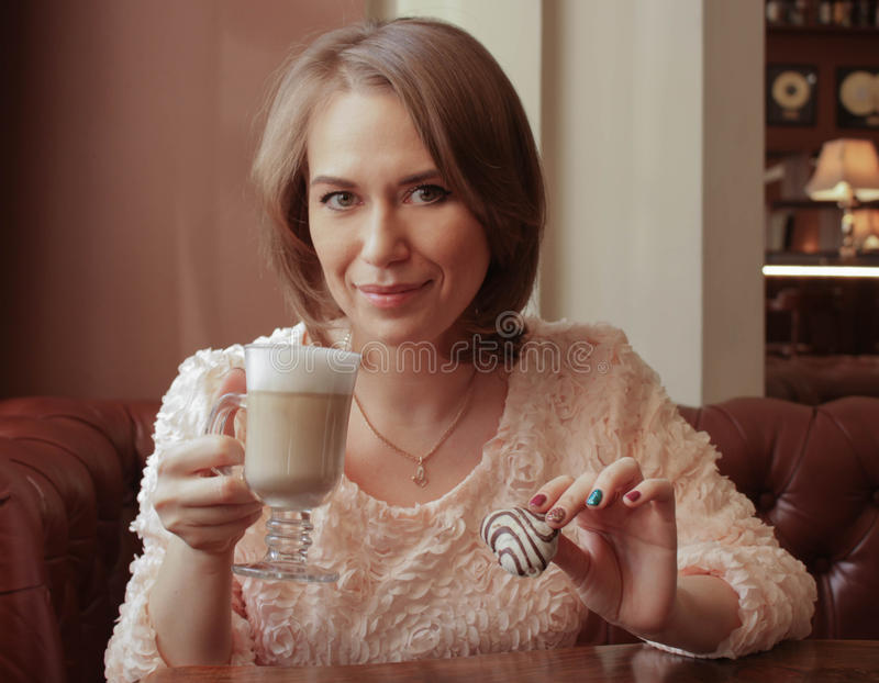 The girl drinks latte with biscuits royalty free stock photos
