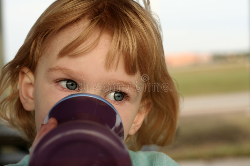 Girl drinks from sippy cup stock photography