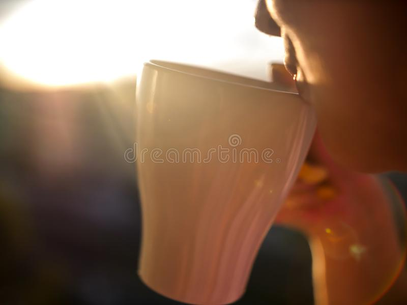 Girl enjoys hot coffee from a white mug at sunset, close-up royalty free stock image