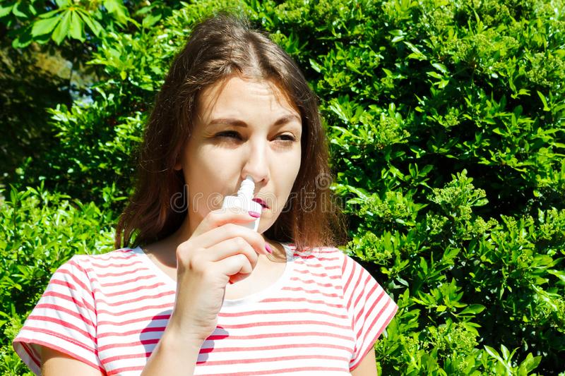 Girl drips blocked nose from allergy. Woman with Respiratory Spray for nose in Spring Blooming. Portrait of a woman having royalty free stock images