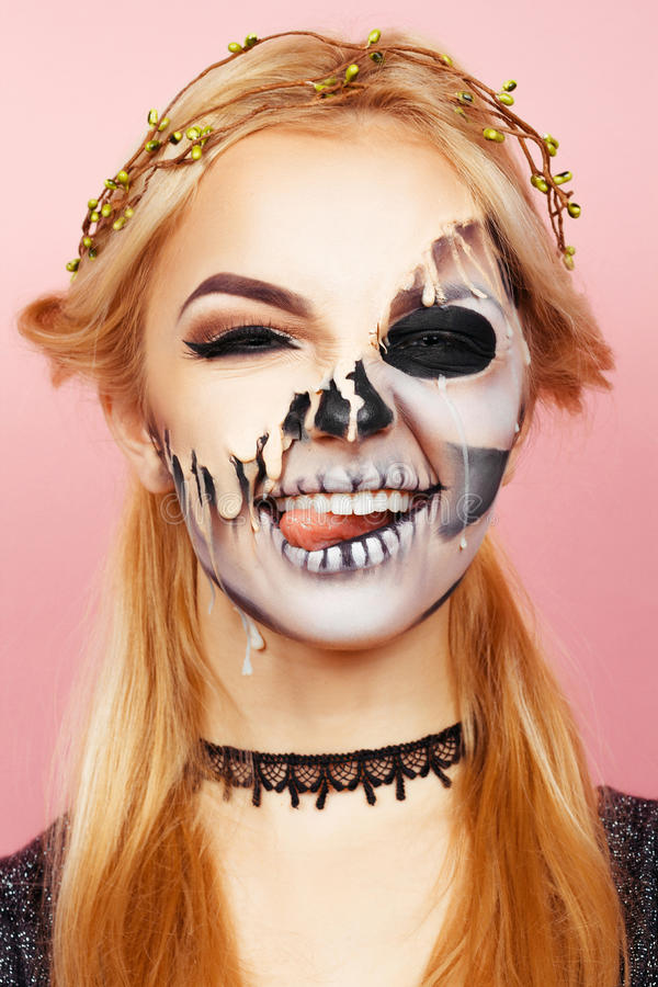 Girl with drips on the face for Halloween. The girl on a pink background with make-up for Halloween stock photography