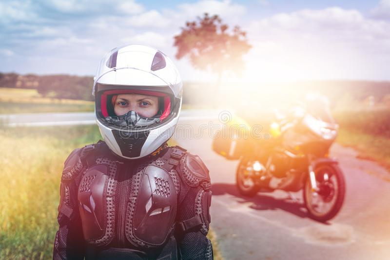 Girl driver portrait, protective equipment, turtle. body armor jacket. Adventure motorbike with bags. a motorcycle tour journey. royalty free stock photography