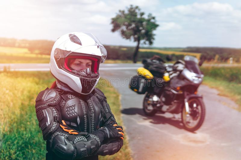 Girl driver portrait, protective equipment, turtle. body armor jacket. Adventure motorbike with bags. a motorcycle tour journey. stock photos