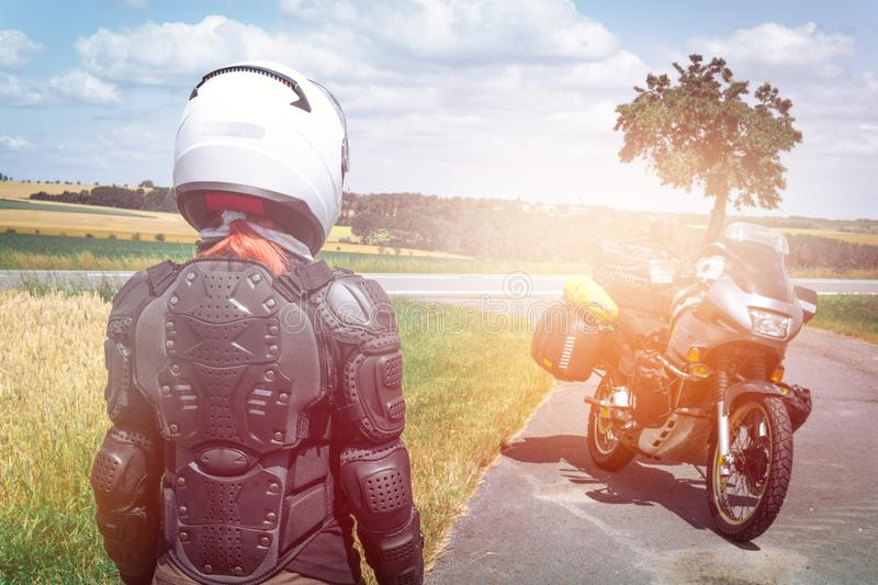 Girl driver portrait, protective equipment, turtle. body armor jacket. Adventure motorbike with bags. motorcycle tour journey. royalty free stock images