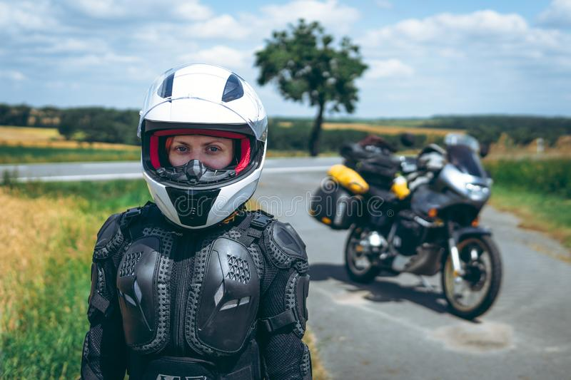 Girl driver portrait, protective equipment, turtle. body armor jacket. Adventure motorbike with side bags. a motorcycle tour royalty free stock photos