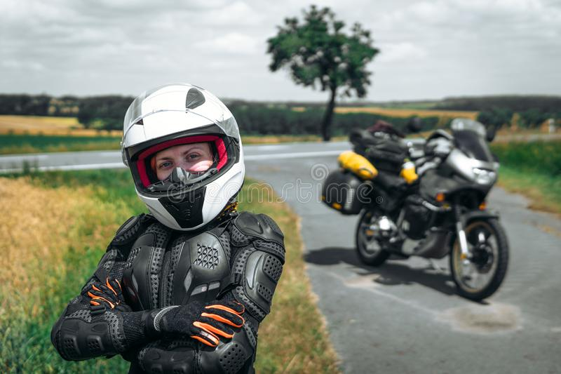 Girl driver portrait, protective equipment, turtle. body armor jacket. Adventure motorbike with side bags. a motorcycle tour stock image