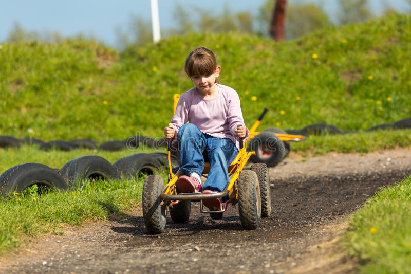 Girl driving buggy cart. Girl having fun driving a buggy cart. Trademarks have been removed royalty free stock photo