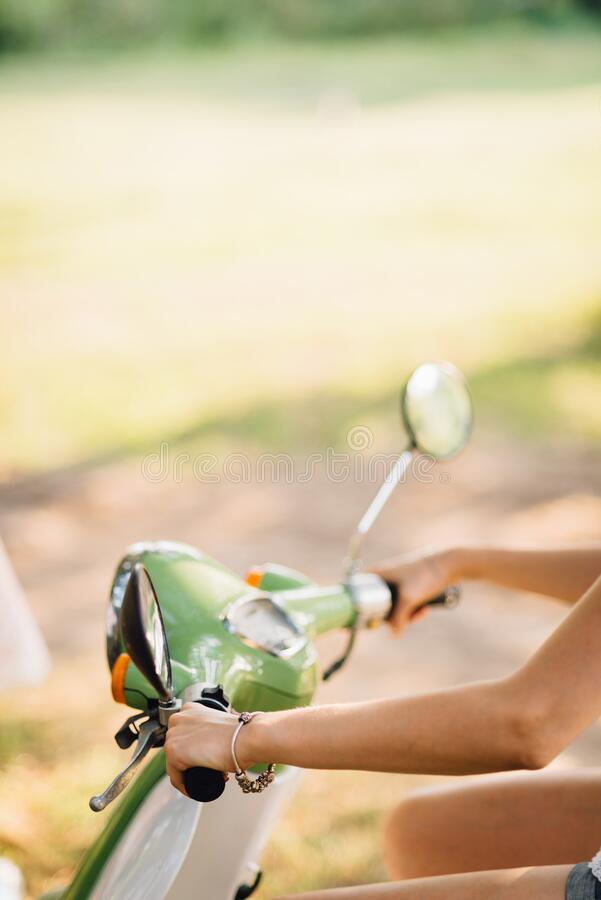 A girl driving a classic scooter. Close - up of girl`s hands stock photos