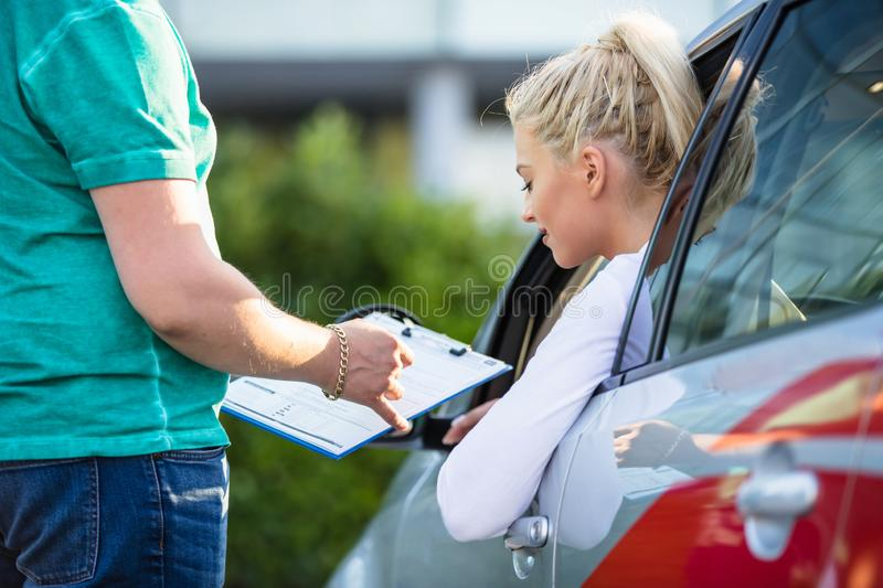 Girl on a driving test with her instructor. Driving school. Young woman on a driving test with her instructor. Learning to drive a car. Instructor of driving stock image