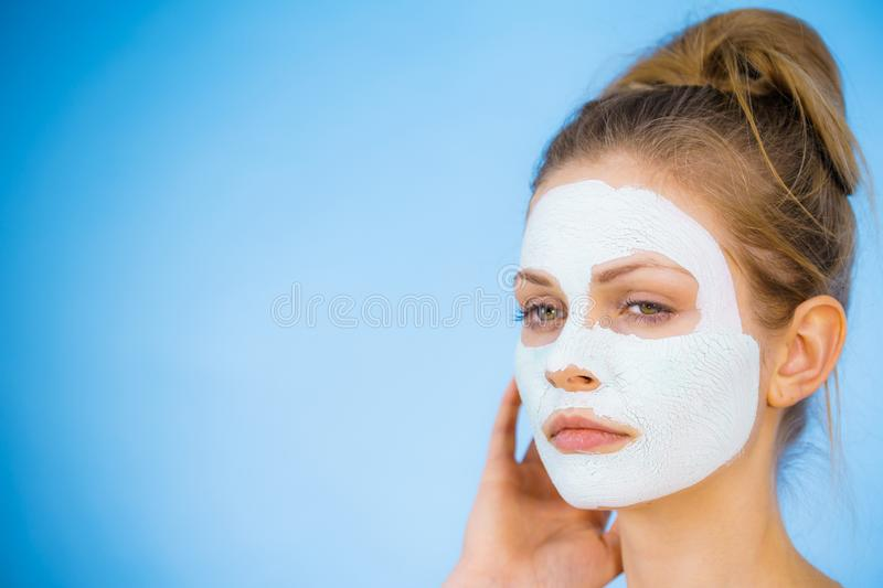 Girl with dry white mud mask on face. Young woman with white dry mud mask on face, against blue. Teen girl taking care of oily skin, cleaning the pores. Beauty stock photos