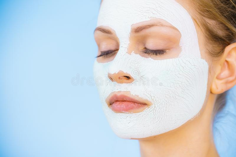 Girl with dry white mud mask on face. Young woman with white dry mud mask on face, against blue. Teen girl taking care of oily skin, cleaning the pores. Beauty royalty free stock photo