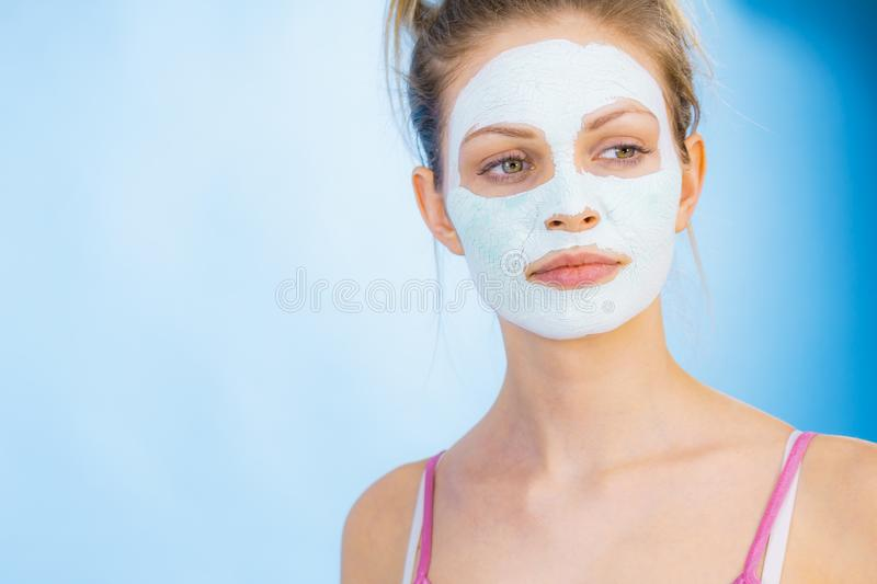 Girl with dry white mud mask on face. Young woman with white dry mud mask on face, against blue. Teen girl taking care of oily skin, cleaning the pores. Beauty royalty free stock images