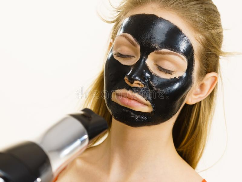 Girl drying peel-off black mask on face. Young woman carbo black peel-off mask on her face, girl drying cosmetic to removing it, using hair dryer. Beauty stock images