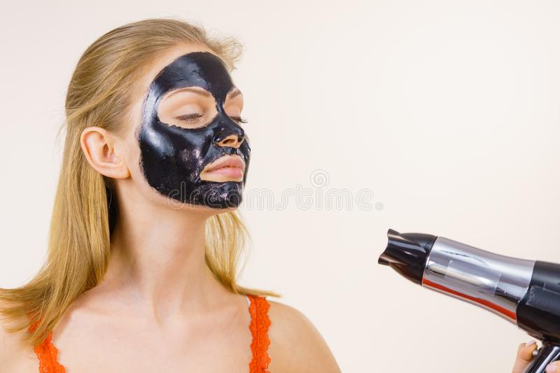 Girl drying peel-off black mask on face. Young woman carbo black peel-off mask on her face, girl drying cosmetic to removing it, using hair dryer. Beauty royalty free stock images