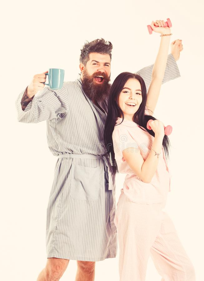 Girl with dumbbell, man with coffee cup. Couple, family on sleepy faces, full of energy. Couple in love in pajama stock photos