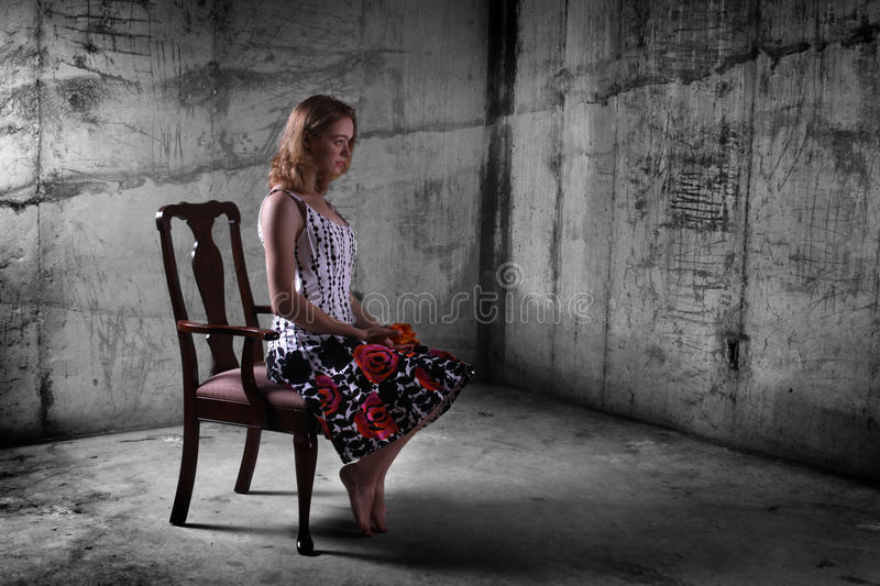 Girl in Dungeon. A young woman sitting alone in a grungy dungeon royalty free stock photography