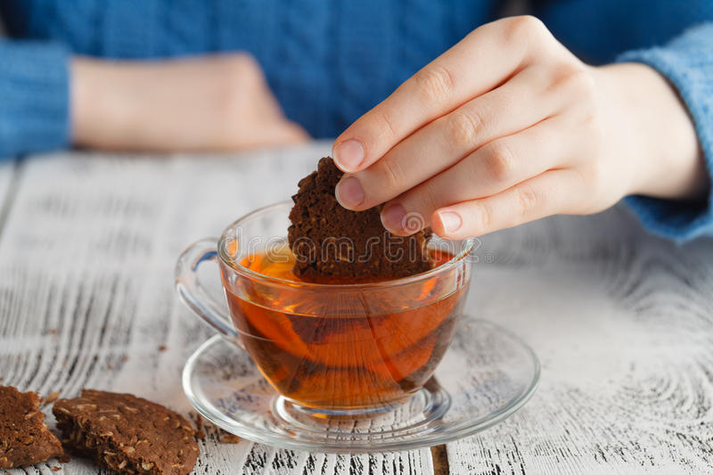 Girl dunk biscuits in tea. Cup on table stock photo