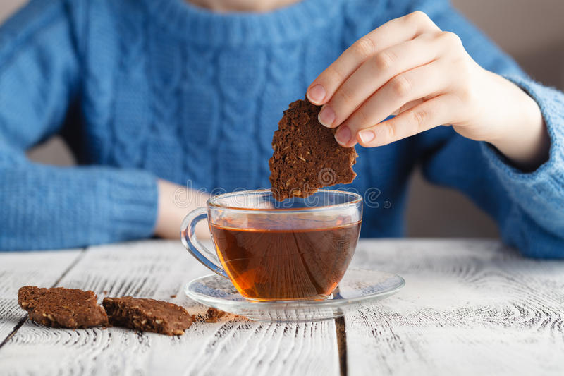 Girl dunk biscuits in tea. Cup on table royalty free stock photos