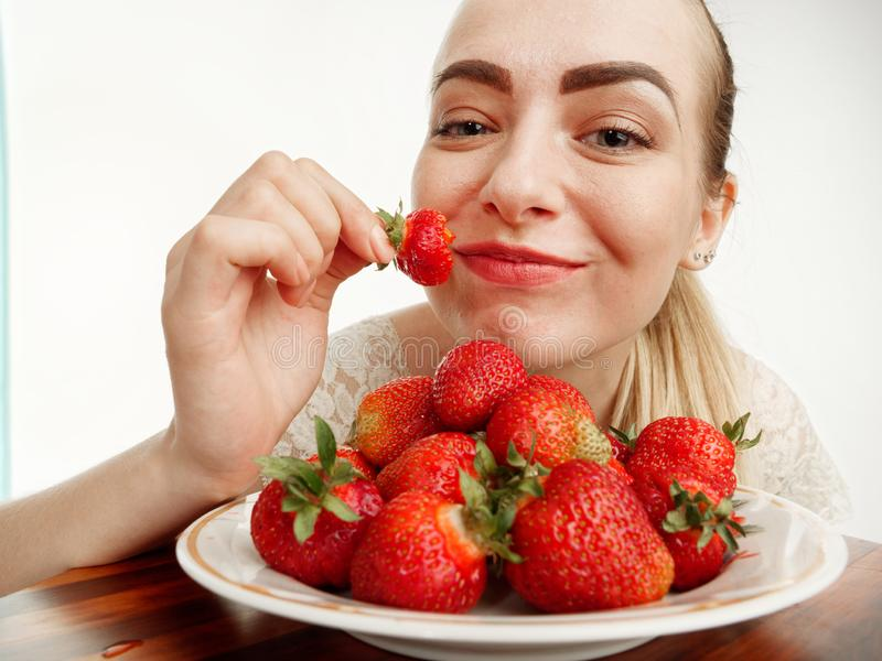 Girl eagerly eating strawberries on white background. 5 royalty free stock photos