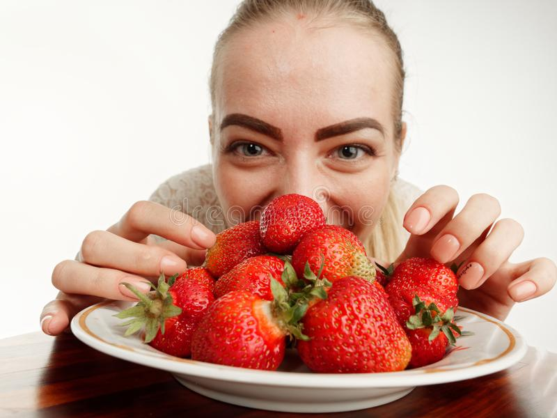 Girl eagerly eating strawberries on white background. 5 royalty free stock photo