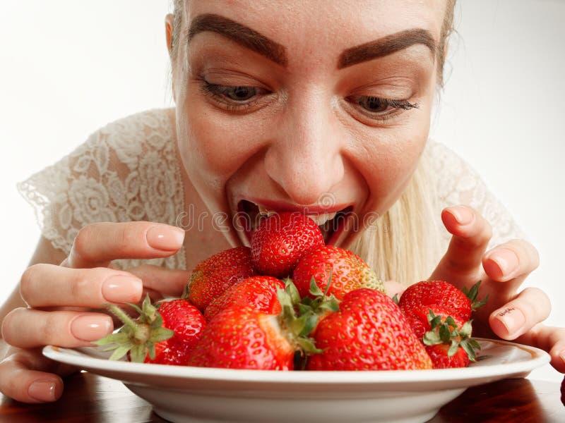 Girl eagerly eating strawberries on white background. 5 stock image